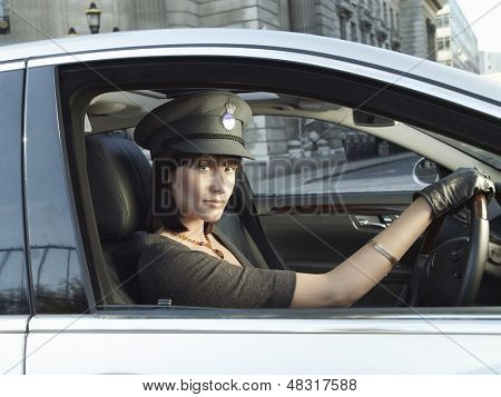 Portrait of female chauffeur in uniform driving a car