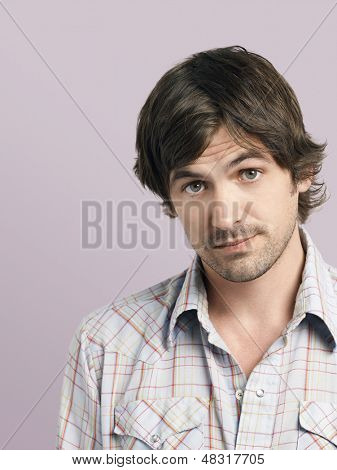 Closeup of confused young man raising eyebrows isolated on colored background