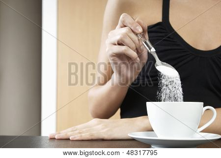Closeup of a cropped woman pouring sugar into tea cup