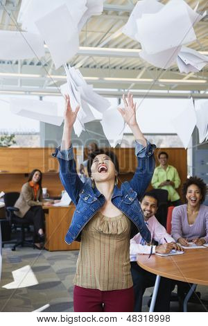 Businesspeople throwing papers in air