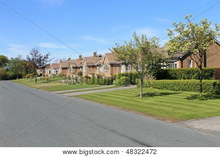 Row of bungalows in village with blue sky background.