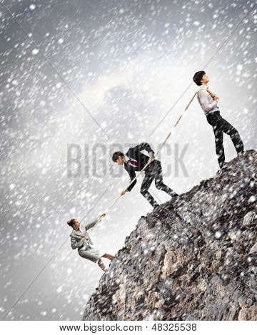 Image of three businesspeople pulling rope atop of mountain under falling snow