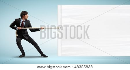 Image of young businessman pulling blank banner. Place for text