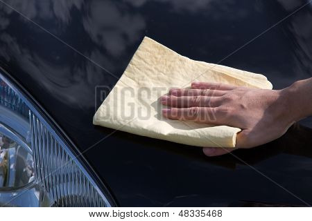 Polishing The Hood Of A Car With A Chamois