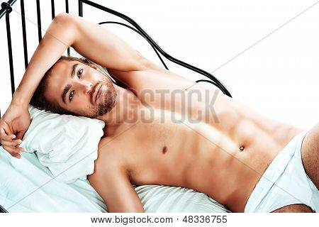 Handsome nude man lying in a bed. Isolated over white.