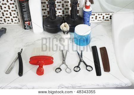 Scissors; combs; razor and brush on counter in barber shop