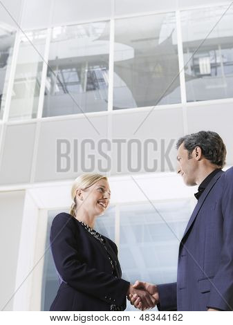 Low Angle View of ein Geschäftsmann und Frau Händeschütteln im Büro atrium
