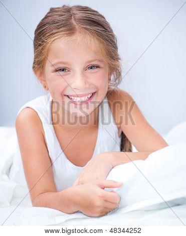 happy little cute girl woke up in white bed