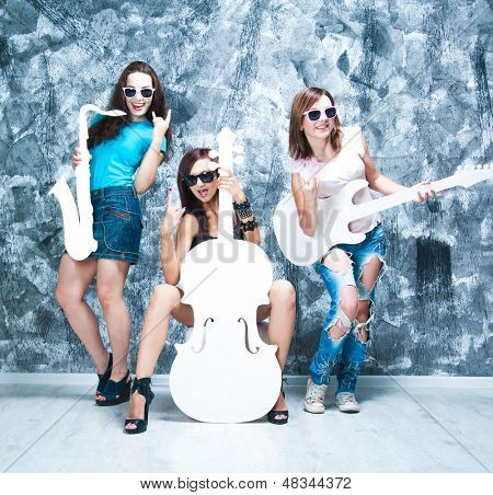 female rock band. girls with musical instruments: guitar, cello and  sax