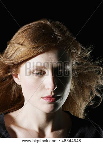 Closeup of beautiful woman with windswept hair looking down on black background