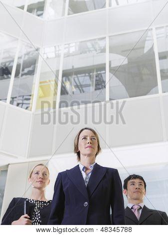 Low Angle View of drei Vertrauen Geschäftsleute stehen im Atrium des Office building