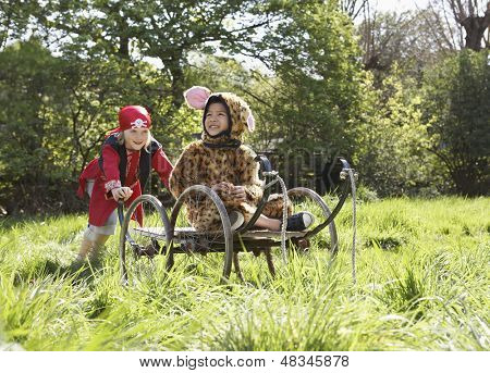 Young boy in pirate costume pushing smiling boy in jaguar costume on cart in the garden