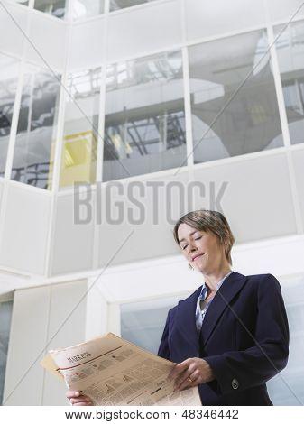 Low Angle View of eine Unternehmerin, die lesen Zeitung im Atrium des Office building