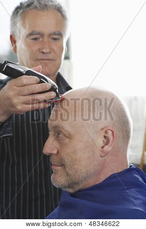 Afeitado la cabeza del cliente masculino con cortador de pelo en peluquería Peluquería