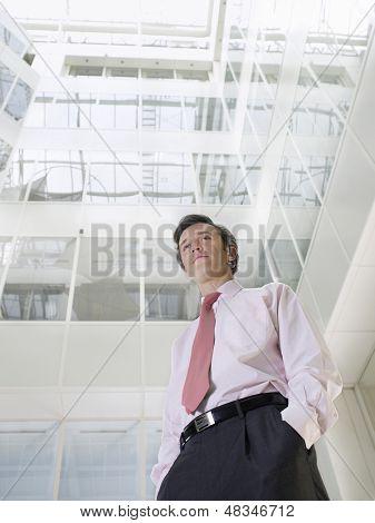 Low Angle View of zuversichtlich Geschäftsmann Stand im Atrium des Office building