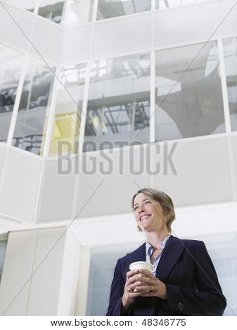 Low Angle Bildniss nachdenklich lächelnd geschäftsfrau hält Essen Kaffeetasse im Atrium der