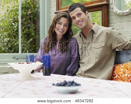 Portrait of a young smiling couple sitting at verandah table