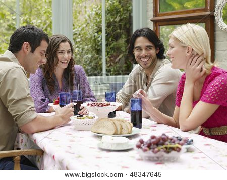 Group of four young people sitting at verandah table