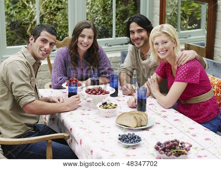 Group portrait of four young people sitting at verandah table