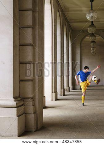 Voller Länge eines Fußballspielers treten Kugel im Portikus