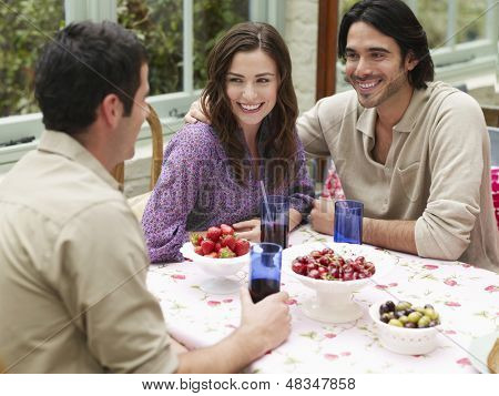 Young multiethnic couple sitting at verandah table with friend