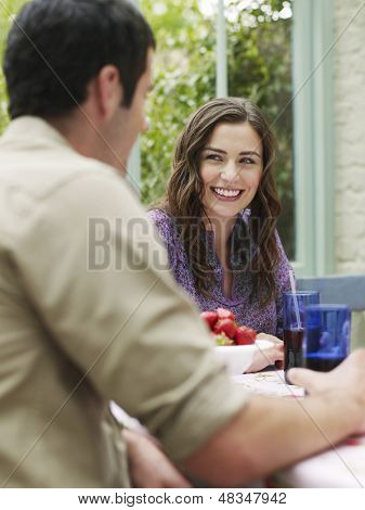 Two young people sitting at verandah table
