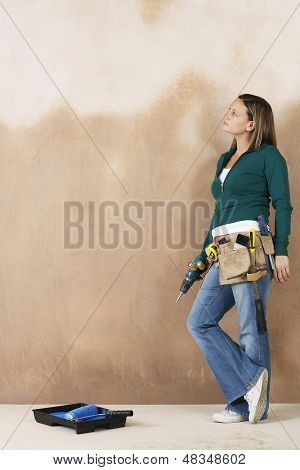 Full length side view of a young woman with toolbelt and drill leaning against wall