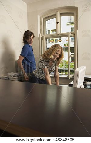 Side view of a man pinching smiling woman's bottom in the office