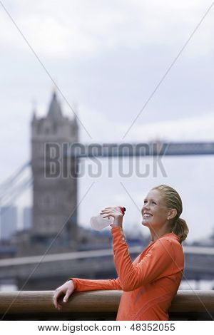 Smiling young woman drinking water in front of Tower Bridge in England