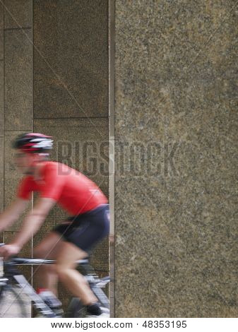 Side view of a blurred man cycling between pillars in portico