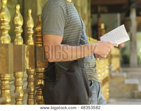 Side view midsection of a young man standing by railing and reading book