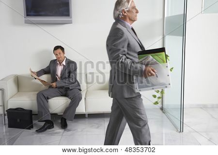 Mature businessman carrying box past a man reading newspaper in office hallway