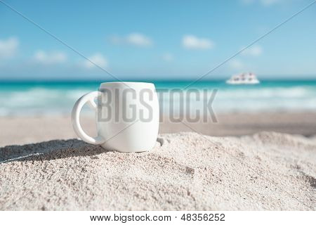 white espresso coffee cup with ocean , beach and seascape. Shallow dof.