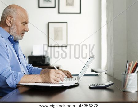 Side view of a mature man using laptop and writing in notepad at home desk