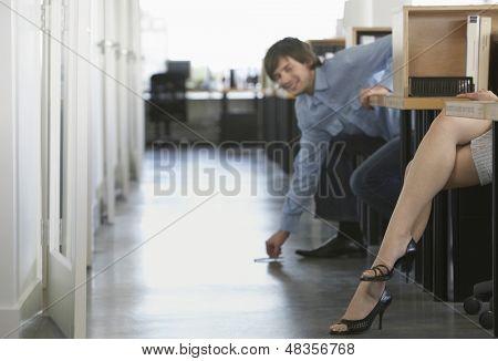Smiling businessman picking pen off floor near woman's legs in office