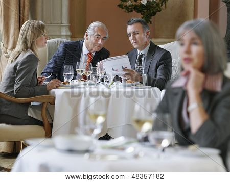 Three businesspeople analyzing documents at restaurant table
