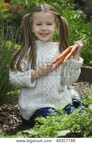 Portrait of a little girl holding carrots in garden