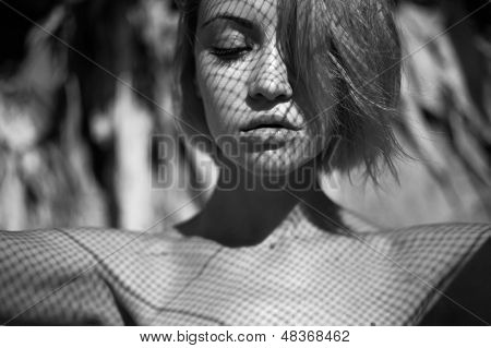 Beautiful young lady with a delicate fishnet pattern on face