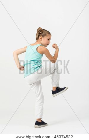A girl with a raised knee standing in a fighting stance