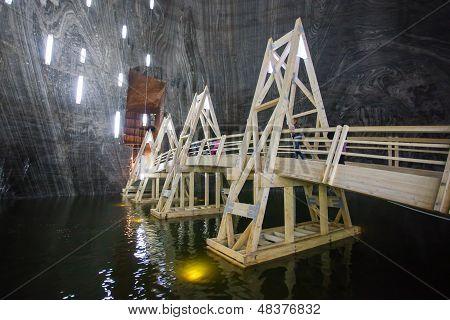 Underground Wood Bridge Over Lake In Turda Salt Mine