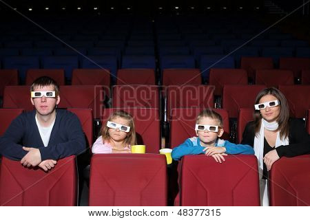 Family watching a movie in 3D cinema with popcorn