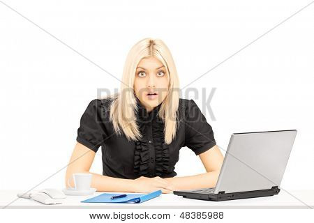 Surpised blond woman sitting on a table in her office, isolated on white background