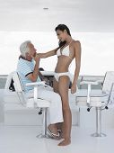 Side view of young woman in bikini romancing with middle aged man at helm of yacht