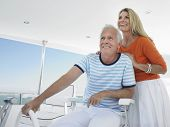 Smiling middle aged couple at helm of yacht