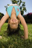 Girl doing back bend in grass