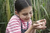 Happy young girl holding frog outdoors