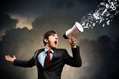 picture of screaming  - young businessman in black suit screaming into megaphone - JPG