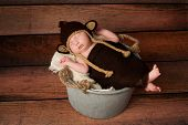 image of baby-monkey  - A newborn baby wearing a crocheted monkey costume and sleeping in a galvanized bucket - JPG
