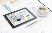 stock photo of pen  - Modern digital tablet with business media website on a screen lying on a desk with some papers and documents pen and cup of coffee - JPG
