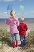 Постер, плакат: Вид сзади брат и сестра проведение рыболовных сетей на пляже